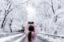 Cute Little Girl Taking Photos On A Snowy Forest Road On A Winter Day