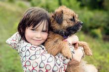 Little Girl Holding Her Border Terrier Dog