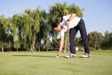 Man Putting Golf Ball On Ground
