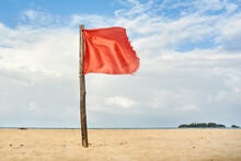 Red Warning Flag On Beach