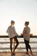 Pensive Barefooted Partners Talking While Having Break In Yoga Training On Beach During Sunrise