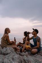 Friends Enjoying Beer And Snacks On Seashore