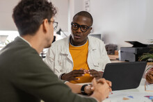 Black Man Discussing Project With Colleague In Workplace