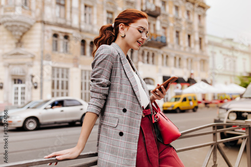 Fotomural Red haired woman in stylish outfit chatting on phone