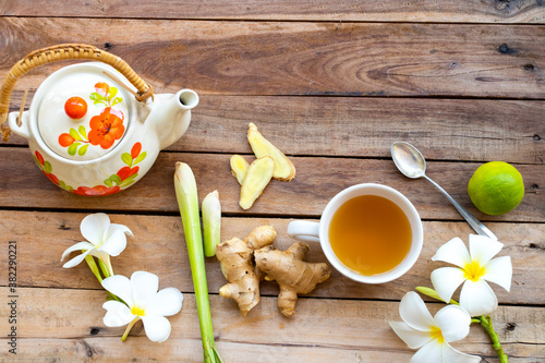 hot ginger water herbal healthy drinks health care for cough sore with ginger slice, lemongrass, lemon, teapot and flowers frangipani local flora of asia arrangement flat lay style on wooden