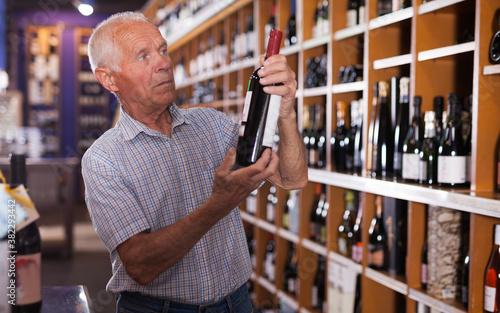 Fototapeta Portrait of senior man visiting winehouse in search of bottle of good wine