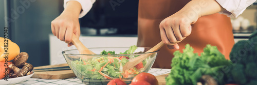 Asian woman is mixing the ingredients in a salad bowl at the kitchen cooking table Billede på lærred