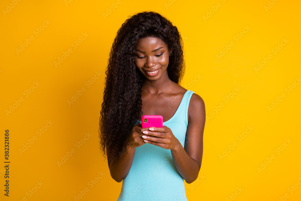 Fototapeta Photo portrait of african american woman holding phone with two hands smiling looking down isolated on vivid yellow colored background
