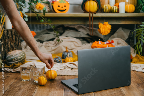 Fototapeta Halloween festivities in new normal, New Trick or Treating Regulations celebrate Halloween safely during COVID 19 pandemic. Open laptop ready for online meeting, pumpkins and festive decor obraz