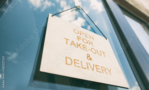 Fotografie, Obraz The wooden sign with text: Open for take-out and delivery hanging on the door in
