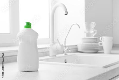 Dishwashing liquid bottle on kitchen sink and clean plates background Slika na platnu