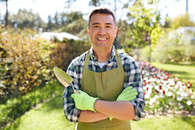 Gardening And People Concept - Happy Smiling Middle-aged Man In Apron With Trowel In Crossed Hands At Summer Garden