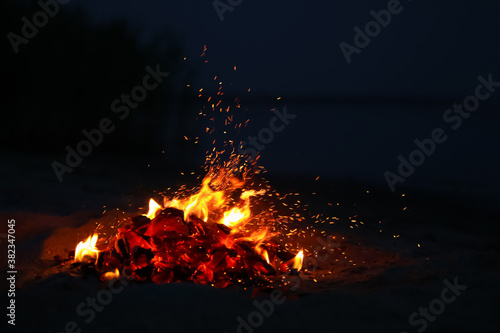Beautiful bonfire with burning firewood on beach at night