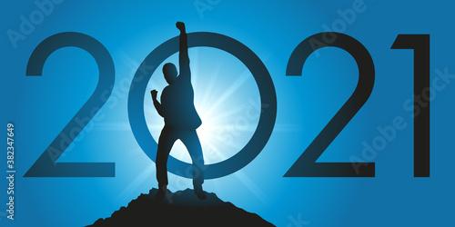 Fotomural Carte de voeux 2021 montrant un homme satisfait en levant le poing en signe de la victoire après avoir atteint son objectif en arrivant au sommet d'une montagne
