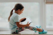 European Little Girl With Tablet Pc Relaxing In A Spacious Room Near The Window