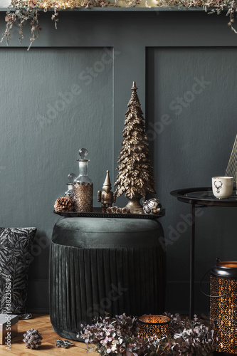 Christmas composition on the green velvet pouf in living room. Beautiful decoration. Christmas trees, candles, stars, lights and elegant accessories. Merry Christmas and Happy Holidays, Template.