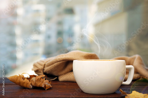 Cup of hot coffee and autumn leaves on window sill indoors. Space for text