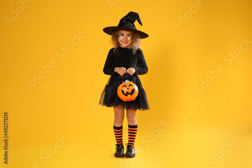 Vászonkép Cute little girl with pumpkin candy bucket wearing Halloween costume on yellow b