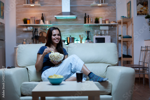 Woman laughing watching tv and eats snacks Canvas Print