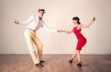 Two swing dancers dancing on a wooden floor