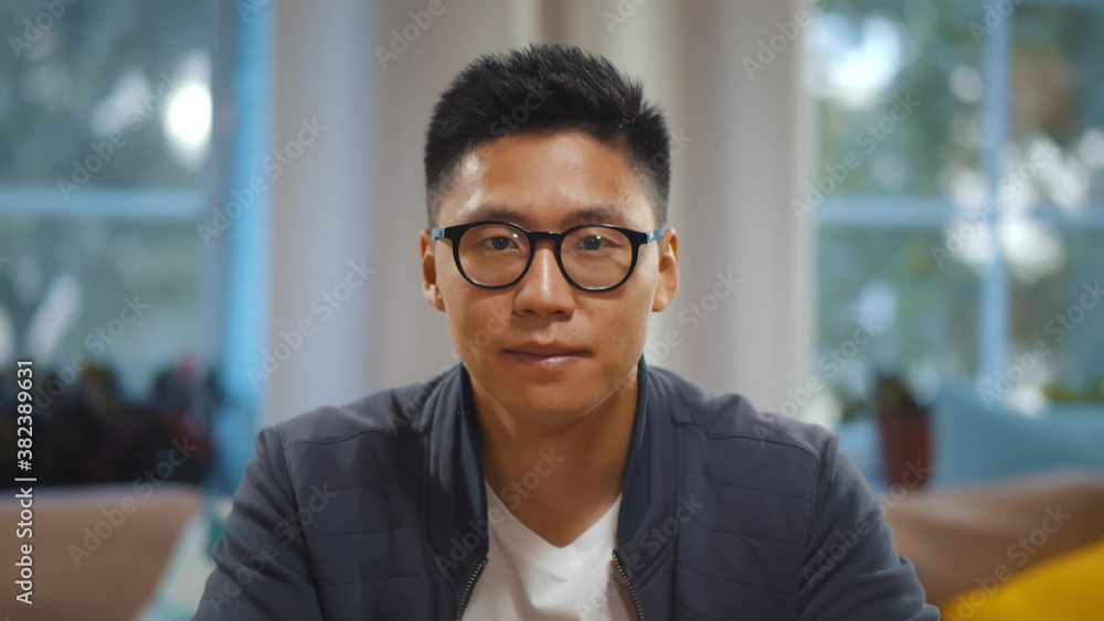 Fototapeta Portrait of asian man in glasses talking online via video call sitting at home