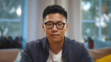 Portrait Of Asian Man In Glasses Talking Online Via Video Call Sitting At Home