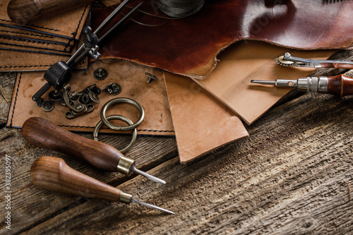 Foto Leather craft tools on old wood table. Leather craft workshop.