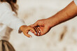 Lovely couple holding hands on white background. Couple together outdoors in love and romantic relationship. Close-up of hands.