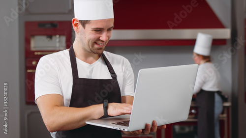 Valokuvatapetti Young smiling male chef in uniform standing in kitchen and working online on lap