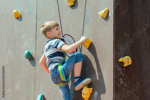 A boy in climbing equipment conquers the top of an artificial to Wallpaper Mural