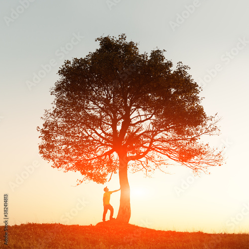 Silhouette of tourist under majestic tree at evening mountains meadow at sunset. Dramatic colorful scene with clear orange sky. Landscape photography