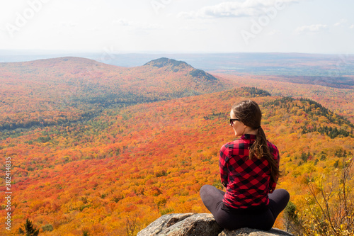 Photo Back view of a young woman sitting in the Mégantic national park and admiring th