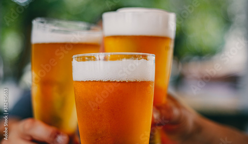 Close-up view of a three glass of beer in hand Canvas Print