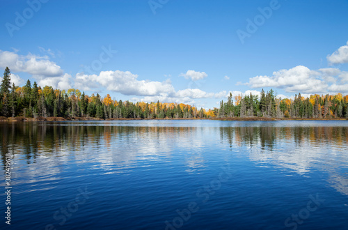Blue lake with treeline in autumn color on a sunny afternoon in northern Minnesota