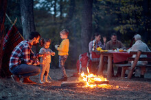 Family Camping In The Woods; Spring Or Autumn Camping With Campfire At Night ; Camping, Travel, Tourism, Hike And People Concept. Quality Family Time Together.