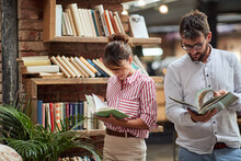 A Young Couple Browsing Books ...