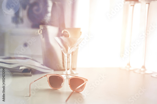 Photo Glasses on the table in the light of the moody sun and the attributes of a woman