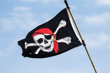 A skull and cross bones pirate flag is flying from a tall ship moored at St Augustine harbor, Florida.