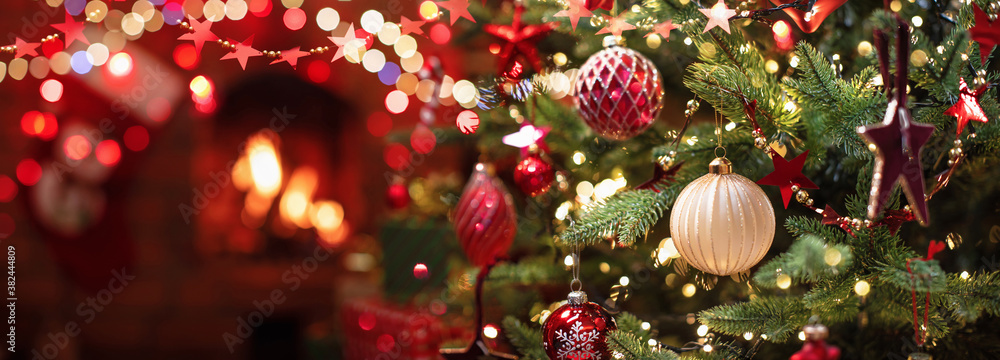 Fototapeta Christmas Tree with Decorations Near a Fireplace with Lights