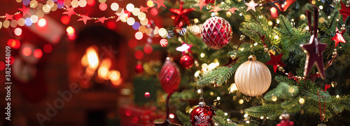 Obraz Christmas Tree with Decorations Near a Fireplace with Lights - fototapety do salonu
