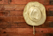 Old Straw Cowboy Hat Weathered, Red Painted,  Wooden Barn Wall, Copy Space