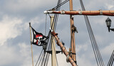 A skull and cross bones pirate flag flying from the rigging of a tall ship replica in St Augustine,  harbor, Florida.