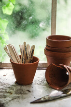 Plant Markers And Pots In Front Of A Greenhouse Window.