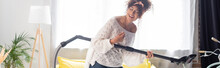 Panoramic Shot Of Curly Woman Having Fun While Holding Vacuum Cleaner And Cleaning Home