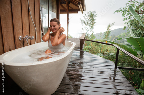 Obraz na plátně Young happy woman pampering her body in water while lie in bath tube outdoor wit