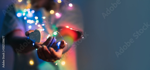 Fototapeta Love symbol. Support compassion. Festive decoration. Heart in caring female hands with Christmas bokeh lights in blur rainbow color gradient glow isolated on navy blue copy space background. obraz