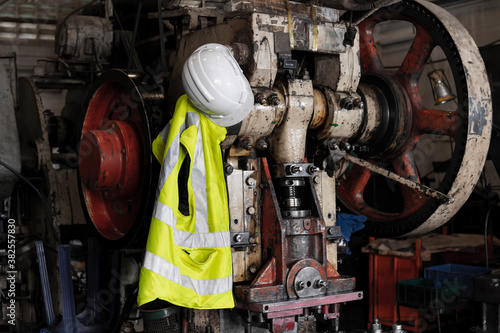 Fototapeta protect safety helmet and safety Vest hang on engineering machine in industrial