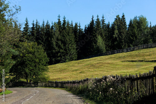 Landscape of road in the moutains with trees and fence