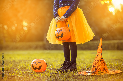 Obraz Halloween kids. Little girl with jack-o-lantern in witch hat with pumpkin candy bucket. Toddler kid in witch costume playing in autumn park. A Child in a carnival costume outdoors  - fototapety do salonu