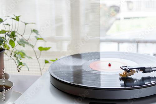 Fotografía 陽が射し込む窓辺のレコードプレイヤーで趣味の音楽を聴く